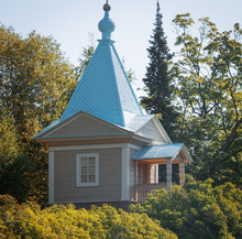 A Small Wooden Chapel With A Blue Roof On A Raised Platform