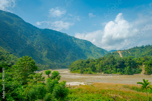 Tuinposter Blauwe jeans Beautiful landscape view, with a river and vegetation in the mountains of Pokhara Kathmandu, Nepal