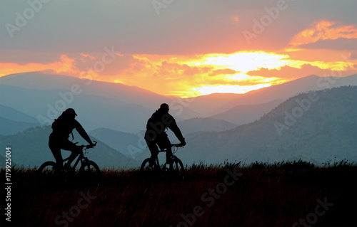 фотографія  Mountain bikers on a trail at sunset