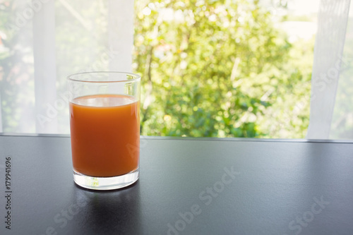 Close up orange juice glass in morning with window view.Healthy drink concepts