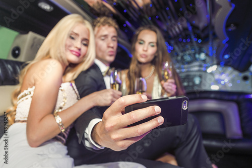 Photo Group of friends taking a selfie in limousine