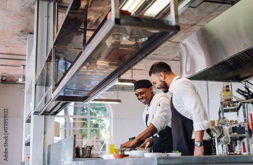 Fotografia  Two cooks preparing food in restaurant kitchen