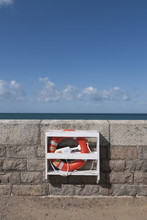 Lifebuoy Ring Fixed To Wall By The Sea In Foregorund Portrait Format