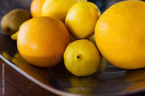 Fototapeta Pomarańczowa cytryna grapefruitowa w metalu naczyniu na drewnianym stołowym świetle dziennym