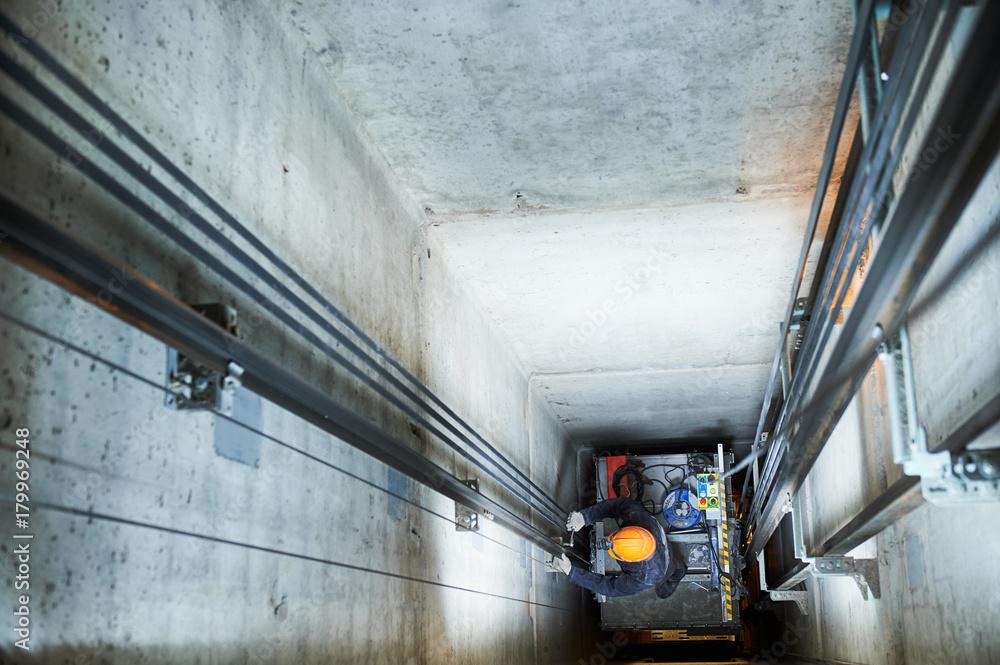 Fototapety, obrazy: lift machinist repairing elevator in lift shaft