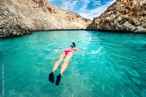 Young woman snorkeling in tropical water. Traveling, active lifestyle concept. Watersports on vacation