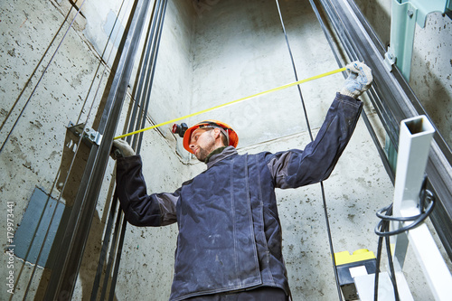Photo  machinist with measure tape checking lift construction in elevator shaft