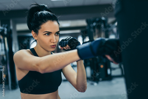 Fotomural Side view of strong attractive brunette woman punching a bag with kickboxing gloves in the gym workout