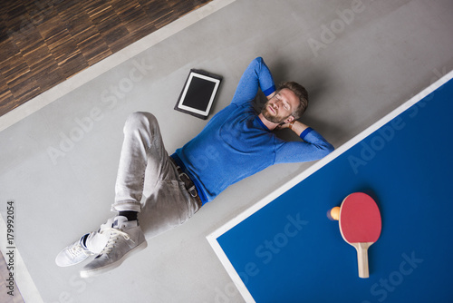 Man lying on the floor with tablet in break room of modern office