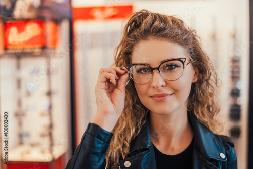 View of a young attractive woman trying glasses at the optician.
