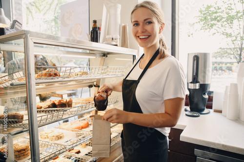 Fotografia Portrait of white Caucasian beautiful barista woman taking muffin pastry from shop-window