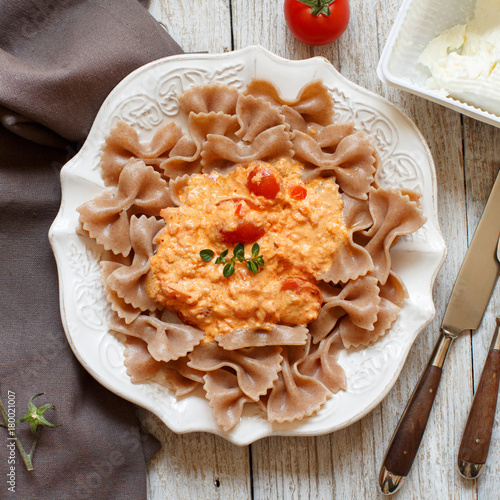 Fototapeta Makaron pełnoziarnisty z serem stracchino i świeżymi pomidorami