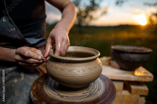 Clay potter creating on the pottery wheel. Sculptor from fresh wet clay on pottery wheel. Selected focus. Hands of young potter was produced on range of pot in open air