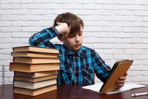 Schoolboy reading electronic book sitting at the library