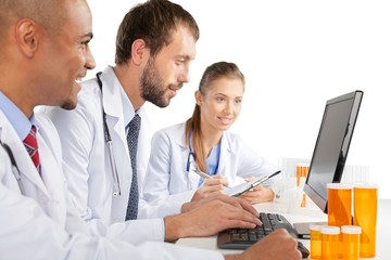 Portrait of Doctors Looking at Laptop and Writing on Clipboard