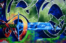 A Fragment Of Detailed Graffiti Of A Drawing Made With Aerosol Paints On A Wall Of Concrete Tiles. Background Image Of Street Art With A Fairy-tale Crystal Sword