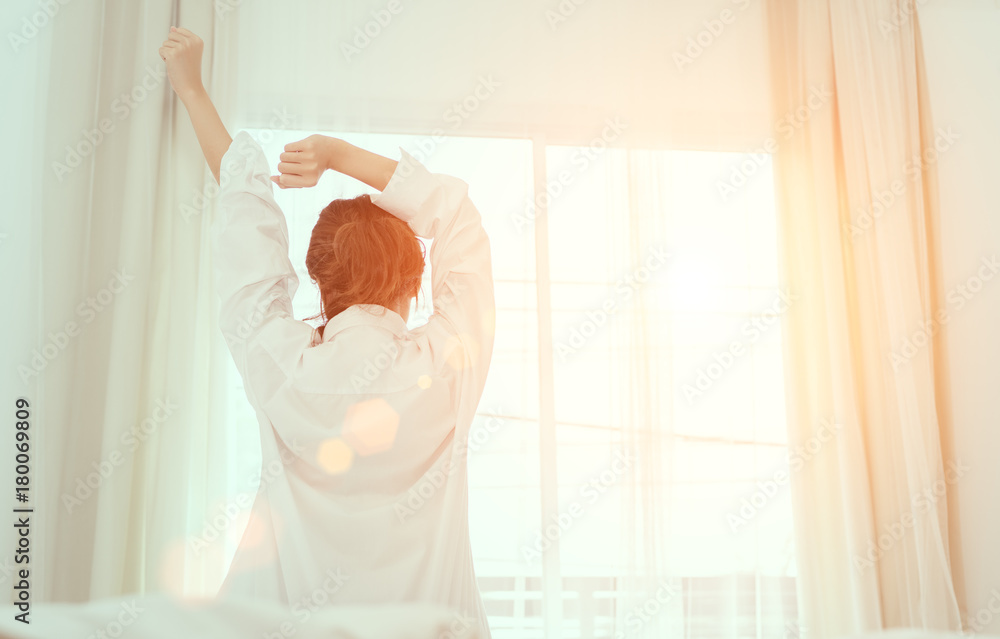 Fototapety, obrazy: Young woman wake up in the morning and sitting on bed at window door side relaxing in holiday with sunlight, back view