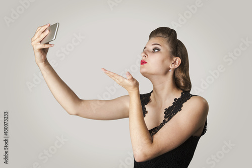 Photo Portrait of a beautiful elegant girl making a self-portrait on a smartphone came