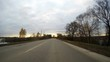 POV car timelapse in autumn overcast day in rural countryside among forests and harvested fields. First snow on road. Yellow leaves on the trees and lying on the road. Village is deserted and old