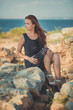 Hot sexy stylish dressed young lady brunette hairs and pinky cheeks with open legs shoulders and arms posing sensuality on sea side rocky beach. seductive woman awaiting her future seaman husband