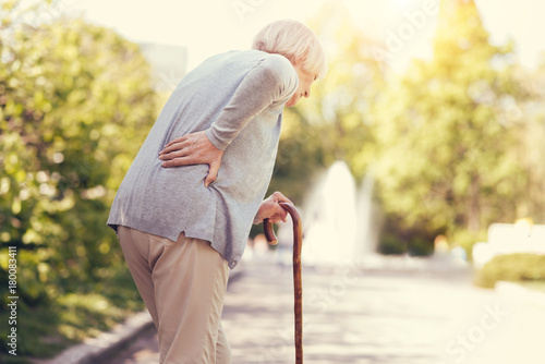 Old age. Sad aged unhappy woman holding a walking stick and walking while feeling pain in the back
