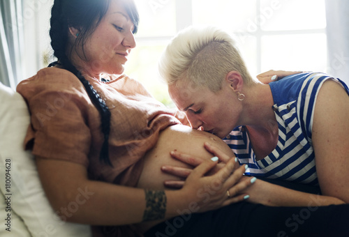 Woman kisses her partner's pregnant belly Canvas Print