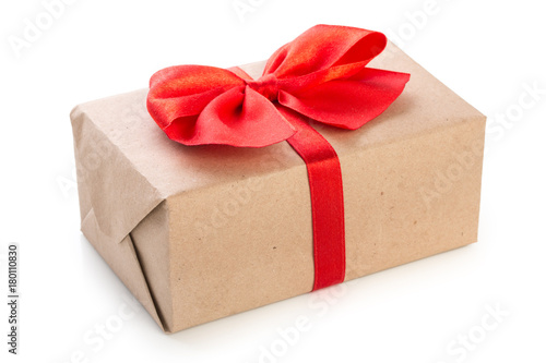 Fotografía  Gift box wrapped in kraft paper with red ribbon bow, isolated on white backgroun