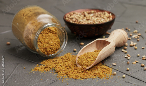 Coriander powder in a glass jar and wooden spoon on black stone table. Spices and condiments. Selective focus