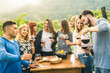 canvas print picture - Group of happy friends having fun outdoors drinking red wine - Young people eating local fresh food at grape harvesting in farmhouse vineyard winery - Youth friendship concept on a vivid warm filter