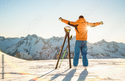 Poster Wintersporten Young professional skier at sunset on relax moment in french alps ski resort - Winter sport concept with adventure guy on mountain top ready to ride down - Backlight view point with bright warm filter