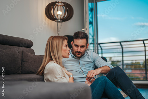 Photo  Loving couple at home enjoying time together, sitting on floor.