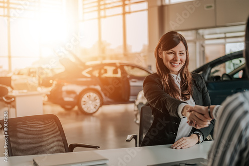 Fototapeta Client shaking hands with car dealer in showroom.