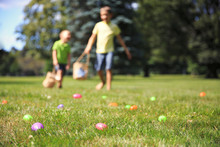 Happy Children At The Easter Egg Hunt. Blurred Background Due The Concept. Kids Have Fun While Searching For Eggs Outdoors