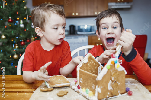children eat gingerbread house and have fun two cute boys enjoy christmas traditions kids