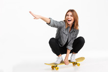 Portrait Of A Happy Cheerful Girl Riding A Skateboard