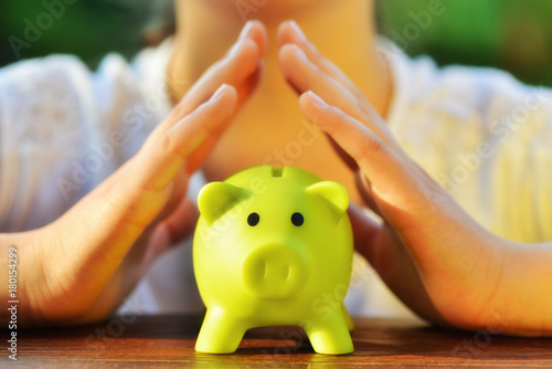 Fotografia  Protect your savings - with hands covering the green piggy bank