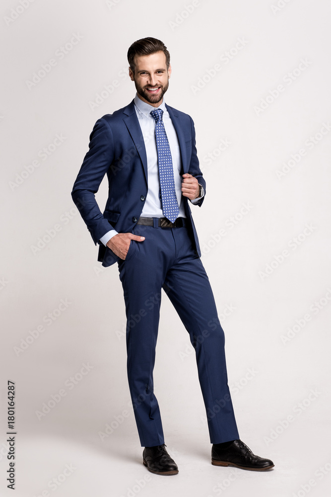 Fototapeta His smile is so cute. Full length of handsome young man in suit looking at camera with smile while standing against white background.