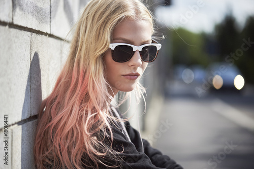 Teenage girl with dyed hair wearing sunglasses
