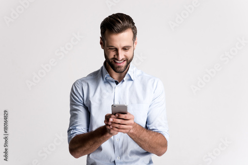 Great news! Handsome young man using his phone with smile while standing against white background.