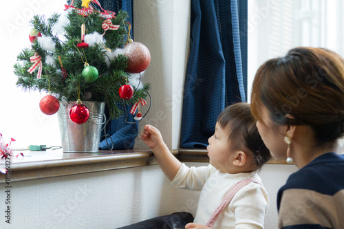 Fotografie, Obraz  クリスマスツリーに飾り付けている母親と1歳の女の子
