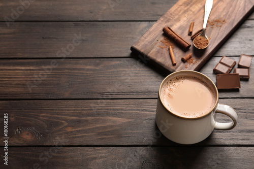 Mug with delicious cocoa drink on wooden background