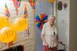 Leinwanddruck Bild - senior woman stands in front of her decorated room door celebrating her 100th birthday