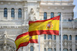 Flag of Spain in the wind in front of Palace of Communication (Spanish: Palacio de Comunicaciones) in Madrid, Spain