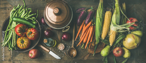 Poster Cuisine Fall cooking background. Autumn ingredients for Thanksgiving day dinner preparation. Flat-lay of green beans, corn cobs, carrot, tomatoes, eggplant, fruits over wooden table, top view