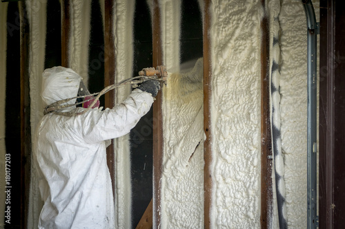 Obraz Worker spraying closed cell spray foam insulation on a home that was flooded by Hurricane Harvey - fototapety do salonu