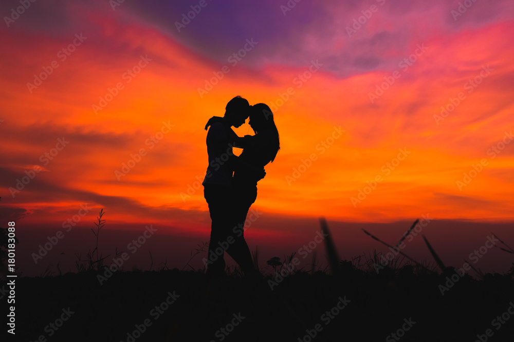 Fototapety, obrazy: silhouette of romantic couple stand hugging on meadow at the sunset time . Have a beauty blue sky.