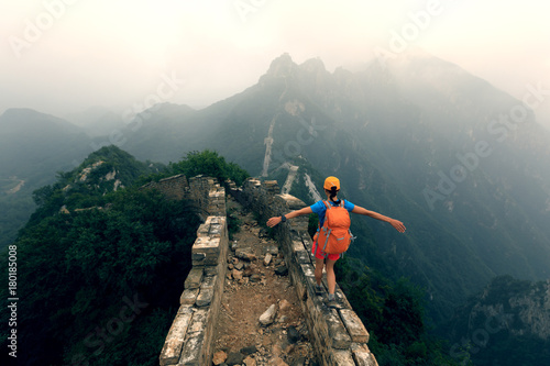 Fototapeta  successful woman hiker open arms to the great wall on the top of mountain