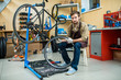 Confident master of bicycle repair sitting by bike with open toolbox