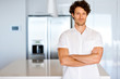 Portrait of a smart young man standing in kitchen