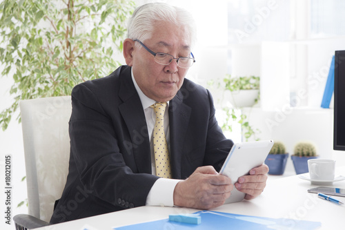 An old man is using a tablet Poster